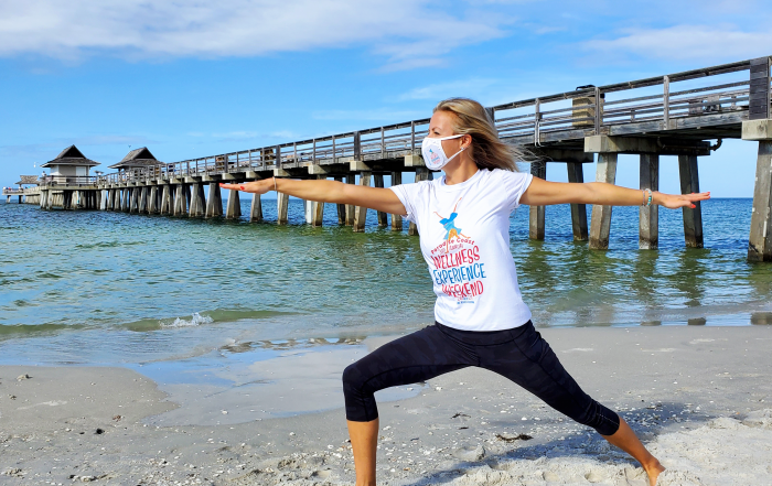 Jen Scev of Yoga 44 strikes warrior pose by the Naples Pier in Florida for Paradise Coast Wellness Experience